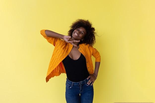 De mooie en gelukkige afrikaanse amerikaan op een gele muur
