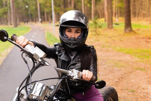 De mooie en gelukkige brunette op een motorfiets