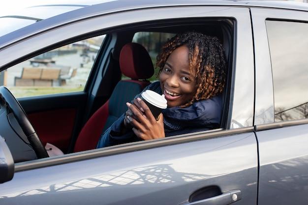 De mooie en gelukkige vrouw in de auto