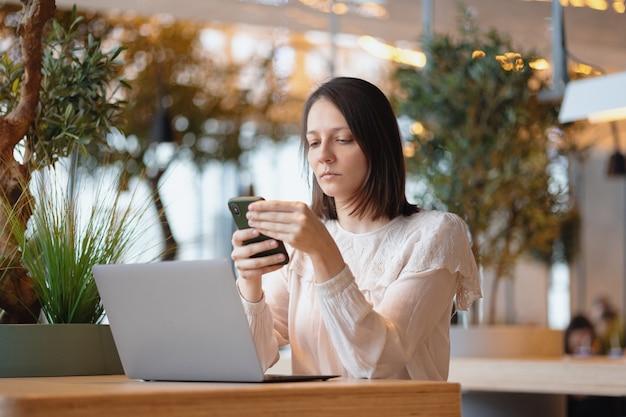 De mooie en jonge europese vrouw werkt op haar laptop in een coffeeshop of openbare plaats