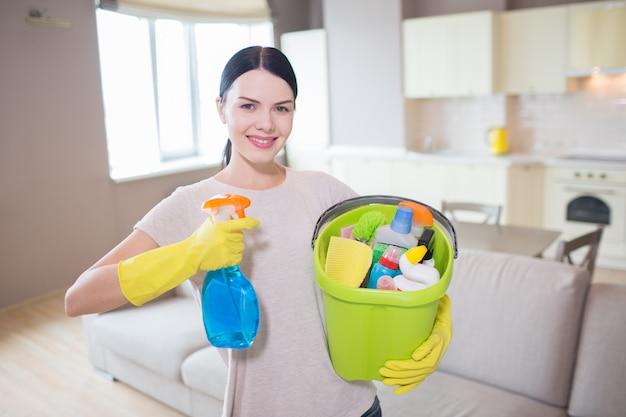 De mooie en positieve vrouw bevindt zich en houdt blauwe nevel en emmer met het schoonmaken van apparatuur in handen. ze kijkt en poseert op camera.
