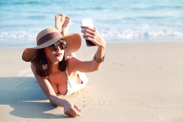 De mooie en sexy vrouw gebruikt celtelefoon terwijl op vakantievakantie zelfportret en het kussen aan camera op het strand doet