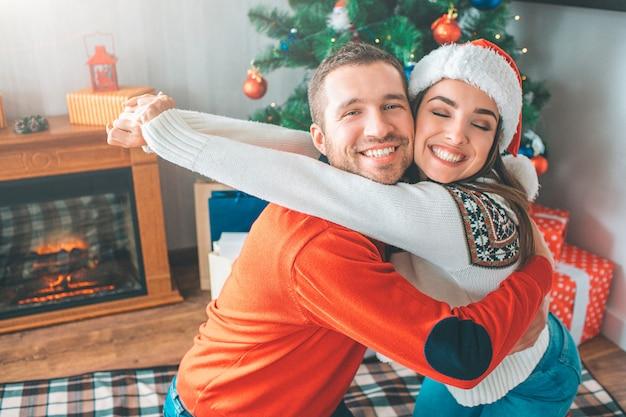 De mooie en vrolijke foto van het jonge paar omhelst elkaar. ze lachen. ze houdt de ogen gesloten.