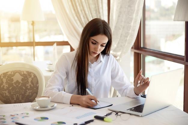 De mooie ernstige vrouw schrijft iets aan het notitieboekje op haar werkende plaats
