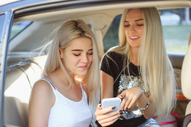 De mooie europese meisjes 25-30 jaar oud in de auto maken foto op mobiele telefoon