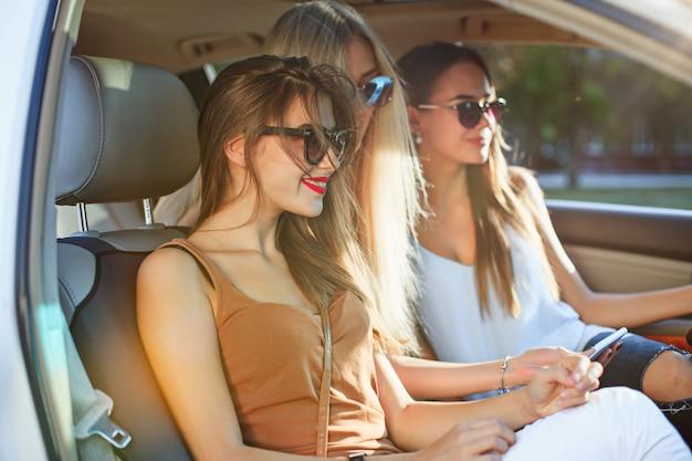 De mooie europese meisjes van 25-30 jaar oud in de auto maken foto op de mobiele telefoon