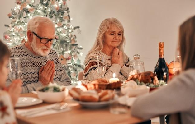 De mooie familie aan het bidden aan de kersttafel