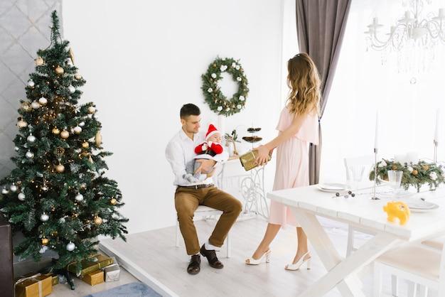 De mooie familie met baby viert nieuwjaar en viert kerstmis in woonkamer met kerstboom. moeder geeft een geschenk aan haar zoontje