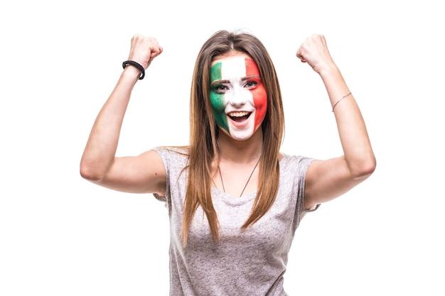 De mooie fan van de vrouwelijke supporter van het geschilderde vlaggezicht van het nationale team van mexico krijgt een gelukkige overwinning die in een camera schreeuwt. fans van emoties.
