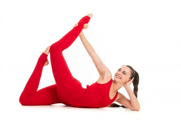 De mooie flexibele vrouw die yoga doet stelt op wit