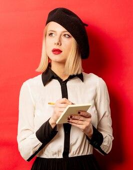 De mooie franse vrouw in baret houdt notitieboekje met potlood op rode muur