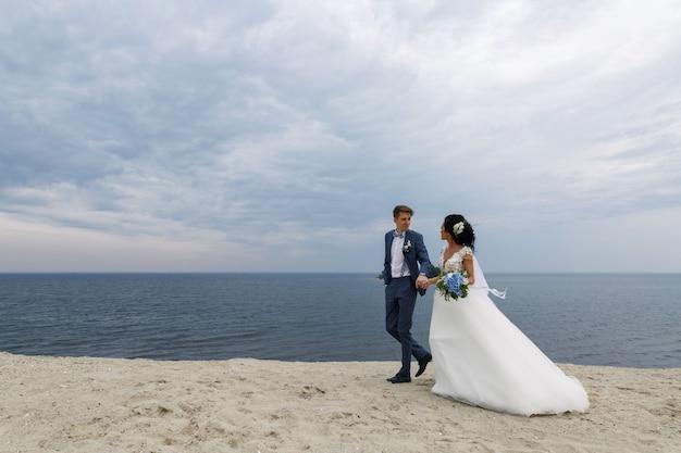 De mooie gelukkige bruid en de bruidegom van het huwelijkspaar bij huwelijksdag in openlucht bij strand
