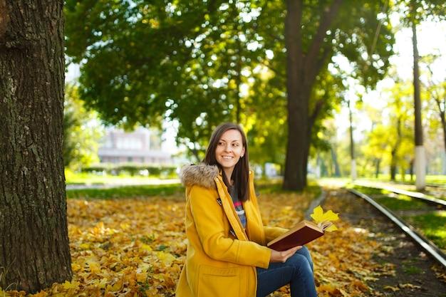 De mooie gelukkige bruinharige vrouw in een gele jas en spijkerbroek zit alleen in het park in de buurt van de tramrails en leest een boek in de warme herfstdag. herfst gele bladeren.