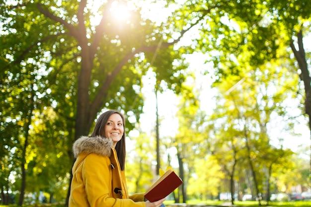 De mooie gelukkige bruinharige vrouw in een gele jas zit alleen in het park en leest een boek in de warme herfstdag. herfst gele bladeren.