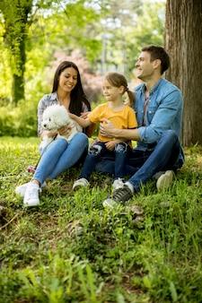 De mooie gelukkige familie heeft in openlucht pret met bishonhond onder de boom