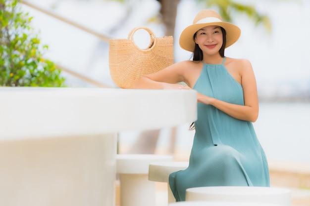De mooie gelukkige glimlach van portret jonge aziatische vrouwen ontspant rond strand overzeese oceaan