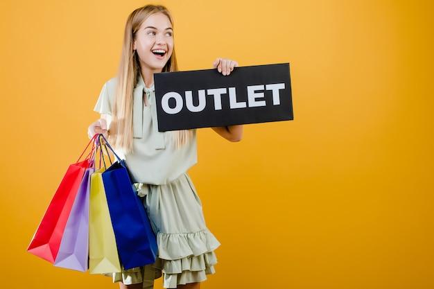 De mooie gelukkige glimlachende blondevrouw heeft afzetteken met kleurrijke die het winkelen zakken over geel worden geïsoleerd