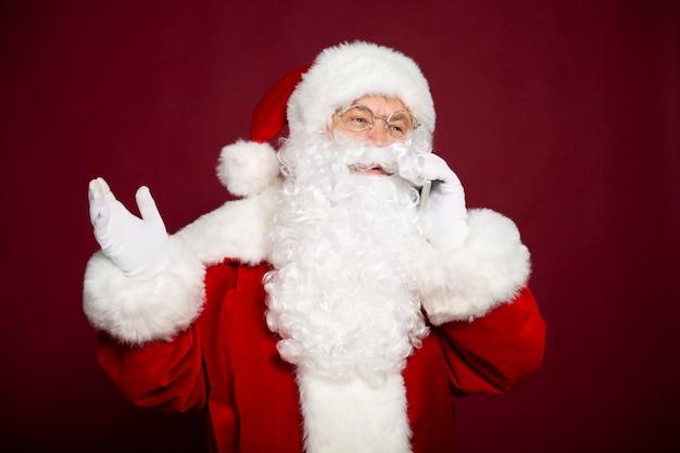 De mooie gelukkige kerstman praat op een smartphone