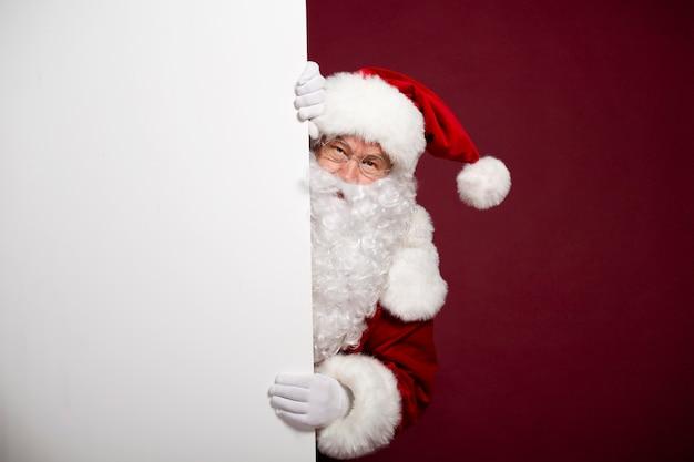 De mooie gelukkige opgewekte kerstman stelt en toont wit leeg bord in handen