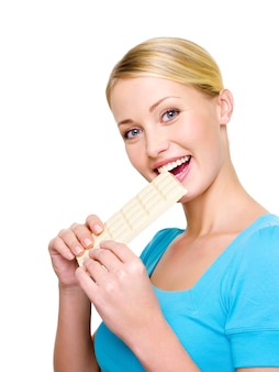 De mooie gelukkige vrouw eet de zoete witte poreuze chocolade - die op wit wordt geïsoleerd