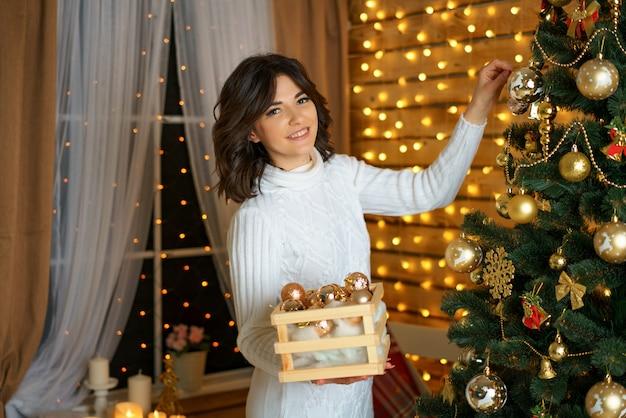 De mooie gelukkige vrouw kleedt kerstboom