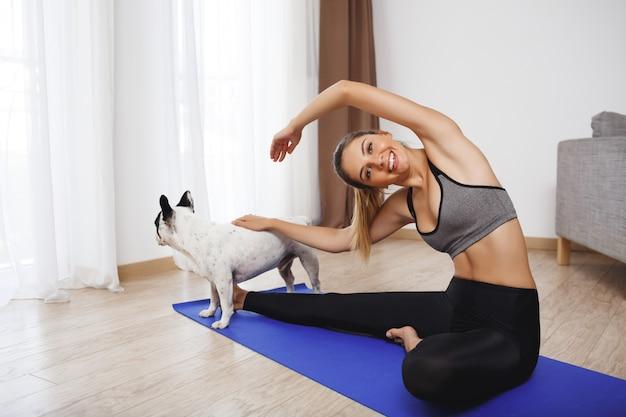 De mooie geschiktheidsmeisjeszitting op vloer met hond en maakt sportoefeningen