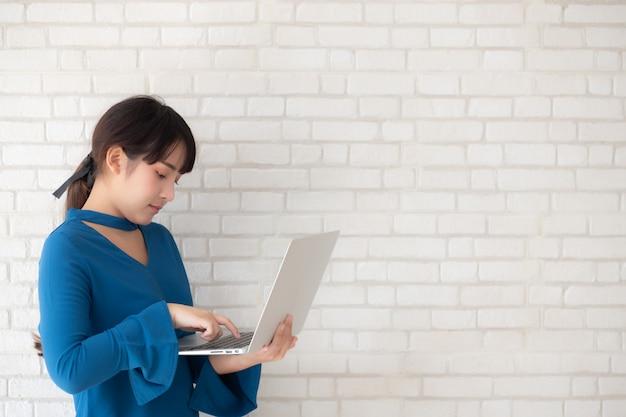 De mooie glimlach die van de portret aziatische jonge vrouw laptop met behulp van