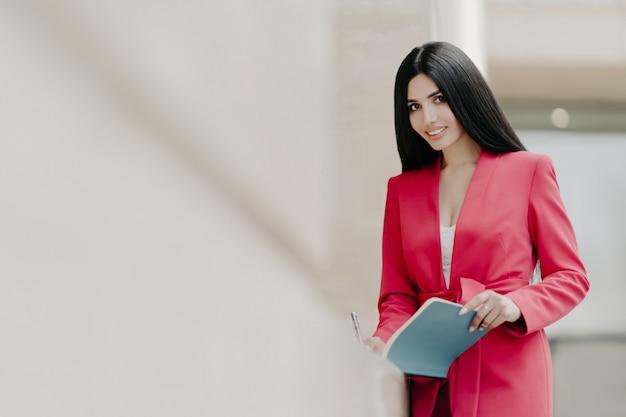 De mooie glimlachende dame in elegant rood kostuum, schrijft sommige nota's in blocnote