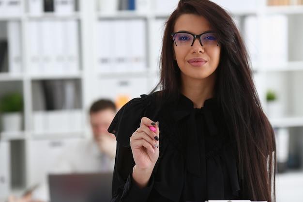 De mooie glimlachende donkerbruine vrouw houdt in wapens roze pen