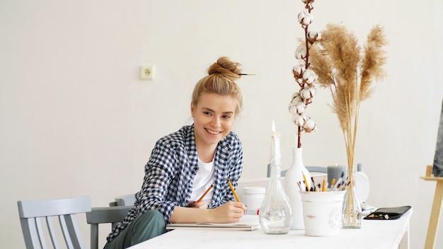 De mooie glimlachende jonge vrouw zit bij een lijst en schrijft plannen op papier met een potlood