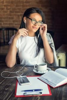 De mooie glimlachende vrouw in glazen luistert muziek door haar smartphone bij koffie.