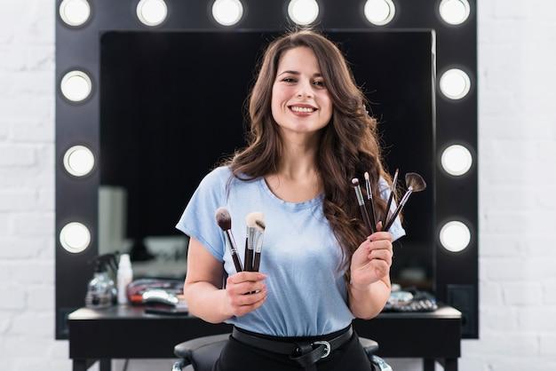 De mooie glimlachende vrouw van de make-upkunstenaar met borstels in handen