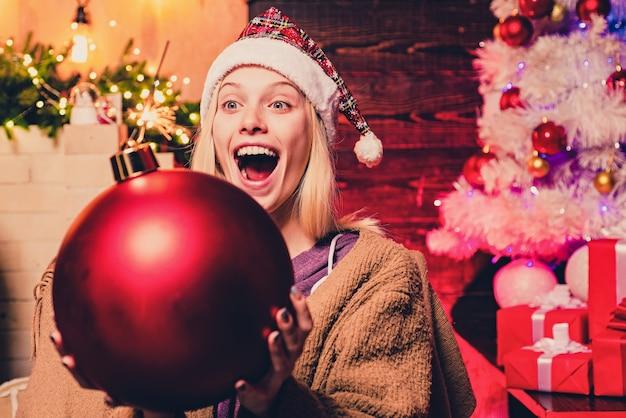De mooie glimlachende vrouw wenst vrolijke kerstmis. winter vrouw met rode kerstmuts. kerstvakantie