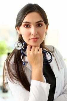 De mooie glimlachende vrouwelijke arts zit op het werk