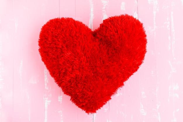 De mooie grote rode vorm van het hoofdkussenhart op roze houten achtergrond