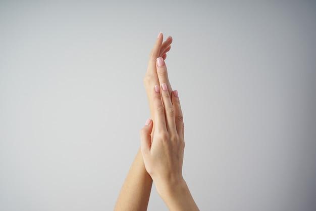 De mooie handen van een jong meisje met mooie manicure op een grijze vlakke achtergrond leggen. spa en manicure concept.
