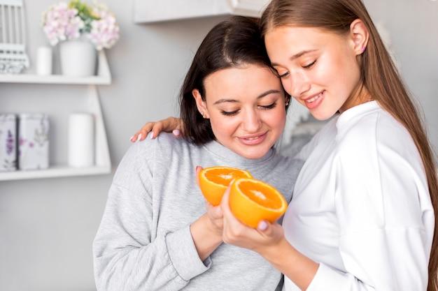 De mooie helften van de paarholding van sinaasappel in de keuken