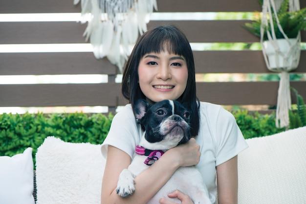 De mooie hond van de meisjesholding op haar handen.