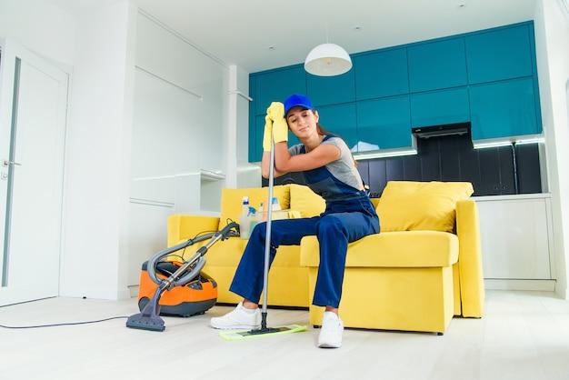 De mooie huisvrouw die het schoonmaken beu is, zit op de bank en leunt naar de dweil nadat ze de vloer heeft gewassen.