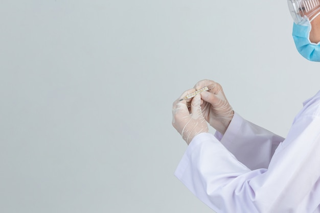 De mooie jonge arts draagt masker terwijl het houden van thermometer met rubberhandschoenen op grijze muur.