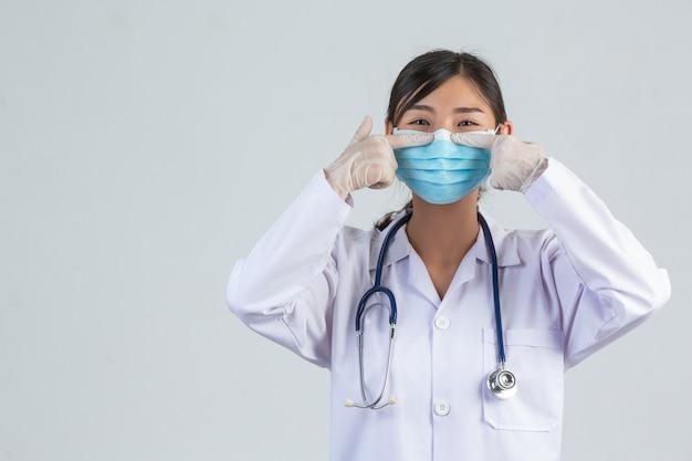 De mooie jonge arts draagt masker terwijl opgeheven haar wijsvinger op witte muur.