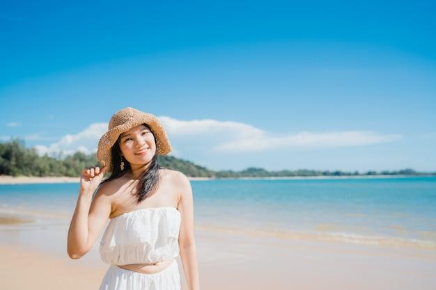 De mooie jonge aziatische gelukkige vrouw ontspant lopend op strand dichtbij overzees.