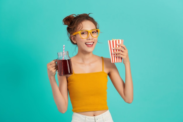 De mooie jonge aziatische popcorn van de meisjesholding en het drinken van soda over blauw.