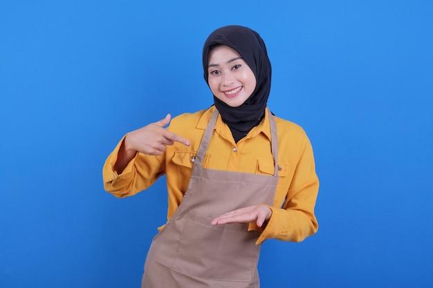 De mooie jonge aziatische schort die van de vrouwenslijtage iets op haar hand toont