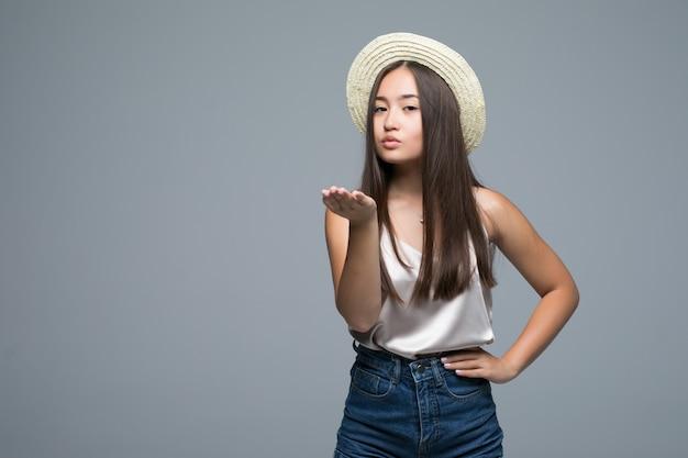 De mooie jonge aziatische vrouw blaast een kus op grijze achtergrond