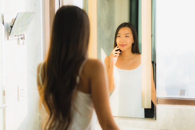 De mooie jonge aziatische vrouw controleert haar gezicht in badkamers