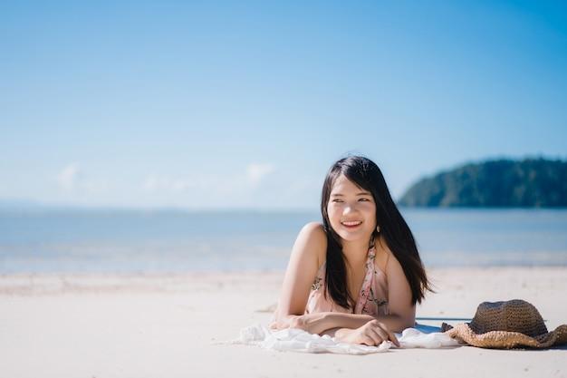 De mooie jonge aziatische vrouw die op gelukkig strand ligt ontspant dichtbij overzees.