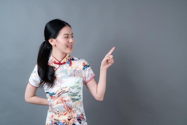 De mooie jonge aziatische vrouw draagt traditionele chinese kleding met hand die aan kant in grijs oppervlak presenteert