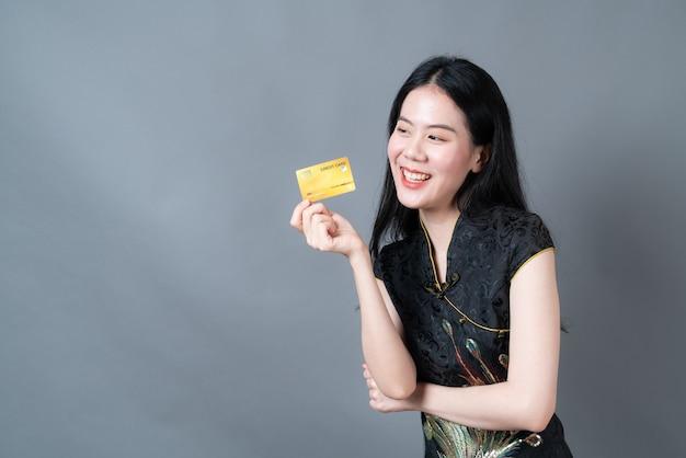 De mooie jonge aziatische vrouw draagt zwarte chinese traditionele kleding met de creditcard van de handholding op grijze oppervlakte