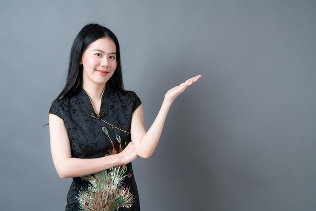 De mooie jonge aziatische vrouw draagt zwarte chinese traditionele kleding met hand die aan kant in grijs oppervlak presenteert